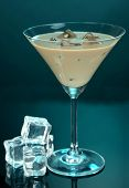 Baileys liqueur in glass on blue background
