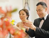 Traditional Chinese wedding tea ceremony, bride and groom, focus on hand and teacup.