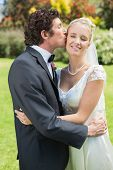 picture of full cheeks  - Groom kissing his pretty new wife on the cheek in the countryside - JPG