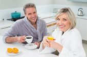 Happy couple in bathrobes having breakfast in the kitchen at home