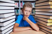 Portrait of serious schoolkid looking at camera surrounded by stacks of books