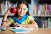 Portrait of happy schoolgirl with big red apple looking at camera in library