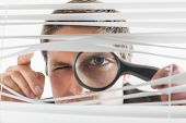 Close-up portrait of a young businessman peeking through blinds with magnifying glass in the office