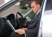 Businessman In Car Checking Email On His Laptop