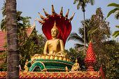 VIENTIANE, LAOS - MARCH 16, 2013: Golden Buddha statue seated on lotus flower at Buddhist temple