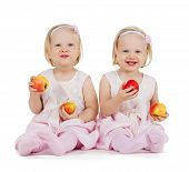 children, food and twins concept - two identical twin girl playing with apples