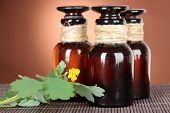 Blooming Celandine with medicine bottles on table on brown background