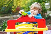 Little Blond Toddler Boy Playing With Toy - Car Park Station In Home's Garden