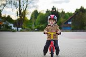 Little Toddler Boy Learning To Ride On His First Bike