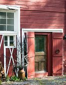 Old Red Barn Entrance with sculptural elements in afternoon light.