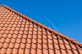 stock photo of red roof tile  - View of a red roof tiles on blue sky - JPG