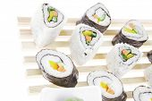 Roll with Cucumber , Cream Cheese with raw Tuna and Salmon inside. on wooden grid . Isolated over wh
