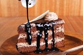 stock photo of brownie  - sweet brownie chocolate cream cake topped with white chocolate and cream with chocolate with chocolate sauce on wooden background - JPG