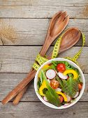 Fresh healty salad on wooden table and kitchen utensil. View from above with copy space
