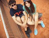 Couple Sitting On A Skateboard On The Tennis Court
