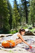 Hiking woman drinking water in river in Yosemite National Park after hiking. Happy girl smiling enjo
