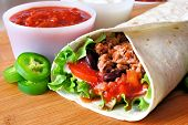 image of tacos  - Close up of a burrito filled with meat and vegetables - JPG