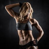 Smiling athletic woman showing muscles on dark background