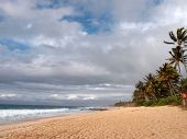 foto of peace-pipe  - Waves lap on Beach at the world famous Banzai Pipeline on a cloudy day on Oahu Hawaii - JPG