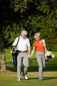 Mature couple playing Golf