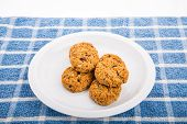 stock photo of baked raisin cookies  - Fresh baked oatmeal cookies with raisins cranberries and nuts - JPG