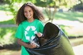 pic of pick up  - Young environmental activist smiling at the camera picking up trash on a sunny day - JPG