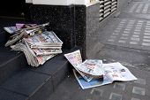 Tabloid Newspapers Abandoned In A Shop Doorway