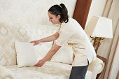 Hotel service. female housekeeping worker maid making order at inn room