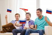 friendship, sports and entertainment concept - happy male friends with flags and vuvuzela supporting