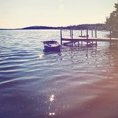pic of dock a pond  - Boat on the lake by the dock in summer - JPG