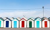Row of beach huts with colourful red blue and green doors
