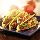 three beef tacos with cheese, lettuce and tomatoes