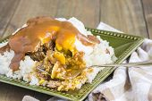 foto of loco  - Loco Moco a traditional Hawaiian dish of teriyaka flavored ground beef patty and a fried egg on a bed of rice smothered in gravy - JPG