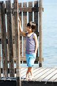 stock photo of dock a pond  - Little kid walking down the bridge on a sea summer dock - JPG