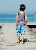 Little kid walking down the bridge on a sea summer dock