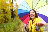 Umbrella woman in Autumn excited under rain on fall day.Beautiful young female wearing raincoat surp
