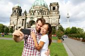 Berlin Germany travel couple selfie self portrait. Happy tourists people in front of Berlin Cathedra