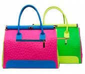 Two bright neon pink, blue and green leather bags with gold lock and ostrich texture leather isolate