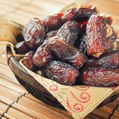 Pile of fresh dried date fruits in bamboo basket. Dried date palm fruits or kurma, ramadan food which eaten in fasting month.