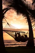 Silhouette of Romantic couple relaxing in tropical hammock at sunset