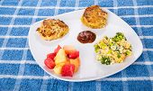 stock photo of crab-cakes  - Two hot crab cakes with cocktail sauce broccoli cheese rice casserole and fresh cut fruit - JPG