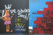 BERLIN, GERMANY - MAY 23, 2014: Fragment of graffiti on Berlin Wall at East Side Gallery - it's a 1.3 km long part of original Wall which collapsed in 1989 and now is largest world graffiti gallery.