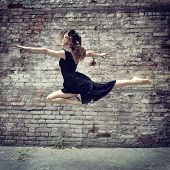 Attractive teen girl dancing outdoor against grunge bricks wall. Toned.
