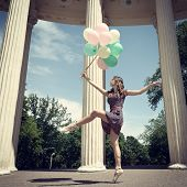 Attractive teen girl dancing outdoor in park against columns with balloons. Toned.