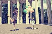 Elegant beautiful teen girl dancer in pointes posing outdoor with little boy holding colored ballons