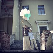 Elegant beautiful teen girl dancer holding colored balloons and posing outdoor with little boy again