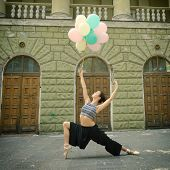 Attractive teen girl dancing outdoor in park against old building with columns holding colored ballo