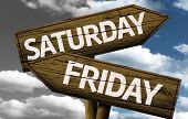 Time concept on wooden sign, Saturday x Friday
