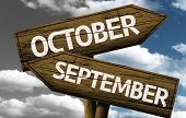 Time concept on wooden sign, October x September