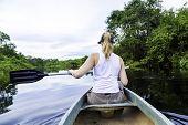 Woman riding canoe in Pantanal River, Brazil